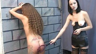 Slim tattooed brunette whipped by leather mistress